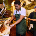 Hector Diaz, a cook at Guacamole 61, makes a burrito at the taqueria that recently opened in the Gourmet Ghetto area of Berkeley